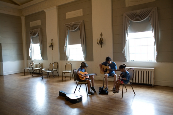 Instructor Christian Sedelmyer teaches a small guitar class at OPFC 2012. Photo by David Pierini, used with permission from The Wednesday Journal.